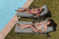 Two diverse female friends sunbathing by pool holding beer