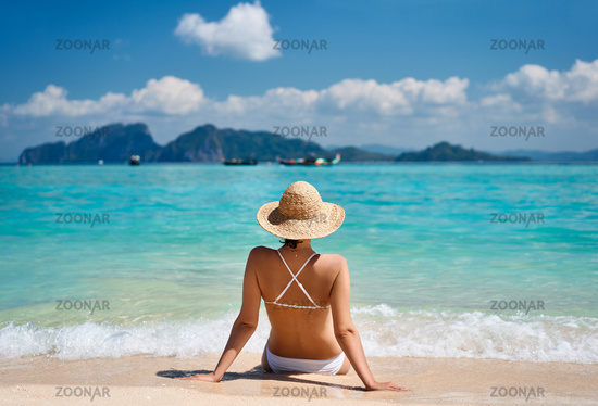 Portrait of a sensual young female in white bikini enjoying warm tropical ocean water.