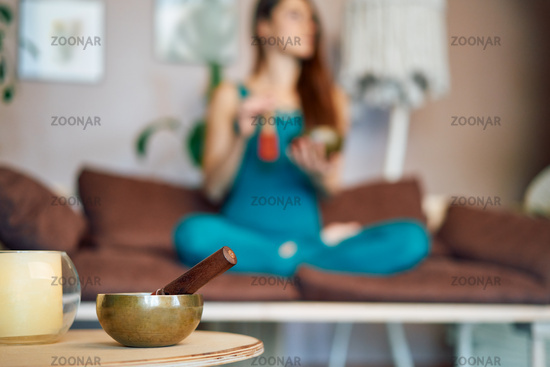 Tibetan singing bowl and woman practicing yoga on background