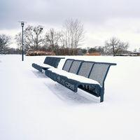 eingeschneite Parkbank in einem öffentlichen Park im Winter