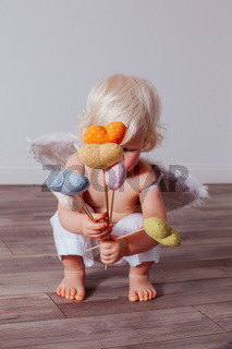 Handmade textile hearts in the hands of little Cupid