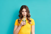 Pretty woman drinking tasty green detox juice on blue background