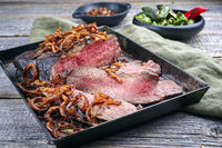 Traditional Commonwealth Sunday roast with sliced cold cuts roast beef with fried onion rings served as close-up on an old rustic metal tray