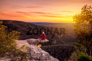Woman watching sunset over mountains landscape