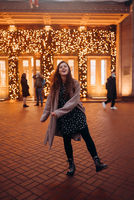 Girl on the background of the illuminated entrance to the building
