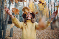 Young woman model in autumn park with yellow foliage maple leaves. Fall season fashion.