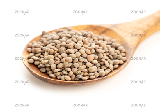Lentil on wooden spoon on white background. Lens culinaris