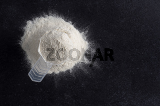 Measuring spoon with protein powder on a dark stone table, nutritional supplement and healthy diet