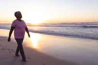 Senior african american woman walking on the beach during sunset