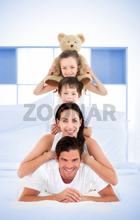 Smiling family leaning on each others shoulders in bed