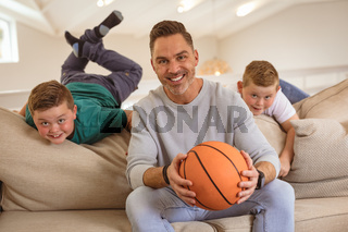 Portrait of caucasian father and two sons with basketball smiling at home