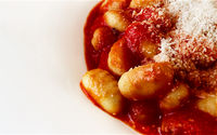 Portion of gnocchi in tomato sauce with grated parmesan cheese served in a white ceramic plate.