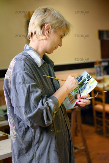 Female creative artist painter concentrated and inspired painting picture with paint brush and oil colors on canvas.
