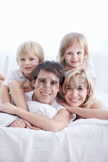 A happy family with two children in the bedroom