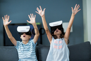 Siblings using virtual reality headset in living room