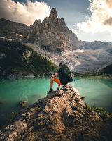 hiker man with backpack at mountain lake lago di sorapis in the dolomites during summer