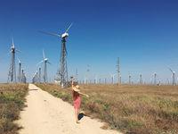 Wind farm, girl walks on the road to the windmills.