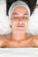 Young woman laying eyes closed, getting facial beauty treatment, view from above.