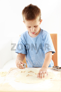 Small boy cutting cookies for Christmas