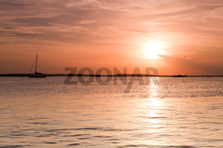 Sailing boat silhouette over sunset