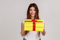 Portrait of smiling dark haired woman giving yellow wrapped present box, congratulating with holiday