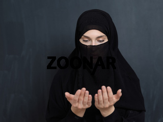 Portrait of young Muslim woman with niqab making dua