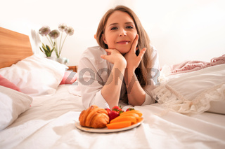 Girl taking photo of plate with strawberries, top view