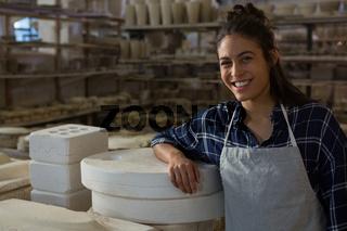 Female potter smiling in pottery workshop