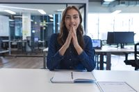Portrait of caucasian female creative worker sitting at desk looking at camera