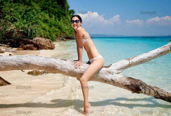 Pretty slim woman in white bikini have fun on tropical beach enjoy her summer vacation at paradise