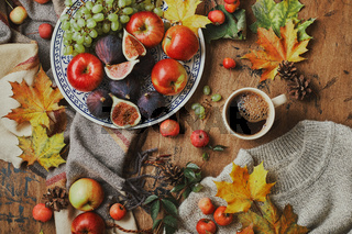 Dish with figs, apples and grapes and cup of coffee on wooden background with a warm sweater, scarf, autumn leaves and apples. Autumn background, top view.