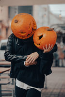 A guy and a girl with a pumpkin heads posing on the street