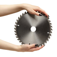 Female hands with black nails manicure with circular saw blade.