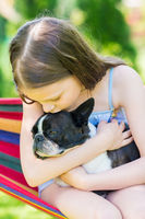 Little girl hugging a Boston Terrier dog in her arms on a hammock