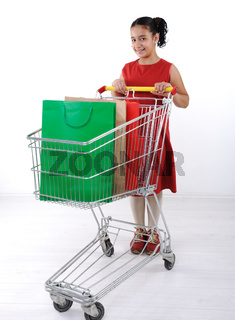 Little girl shopper in red dress with shopping cart