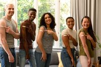 Group of happy diverse female and male friends showing plasters after vaccination