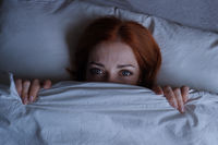 sleepless woman lying in bed hiding under duvet at night