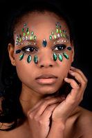 Gesicht einer schoenen jungen farbigen Frau mit Edelsteinen besetzt