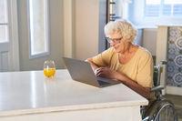 Glückliche Seniorin im Rollstuhl beim Videochat am Laptop