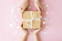 Hands giving paper gift box with ribbon, star, circle paper confetti or glitters