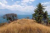 Hill with dry grass at lake Atitlan at a sunny place in nature, San Pedro la Laguna, Guatemala