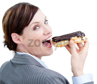 Glowing businesswoman eating a chocolate eclair against a white background