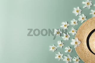 Summertime concept on green background, straw hat and flower heads of daffodil