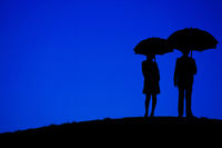 Men and women holding an umbrella stand on the night of the hills