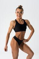 Smiling sportswoman in underwear standing in studio