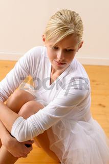 Beautiful ballerina rests sitting on studio floor
