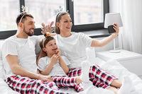 family in pajamas taking christmas selfie in bed