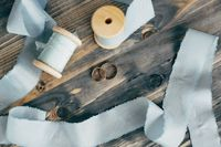 Top view of wedding gold rings on a wooden surface with gray ribbon spools.