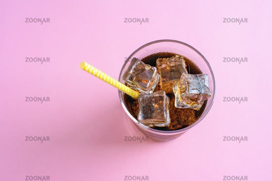 Top view of a glass of cola with ice cubes on pink background