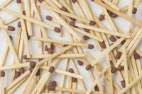Strewn, brown-tipped, wooden safety matches on white